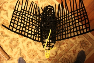 Pipe cleaner eagle frame under construction, showing the top of the bird and wings